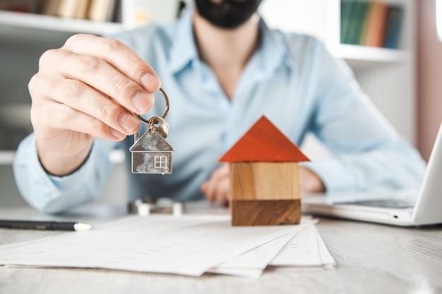 Clé de main de l'homme avec le modèle de la maison sur le bureau