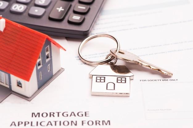 Clé de maison sur demande de prêt hypothécaire avec maison modèle et calculatrice