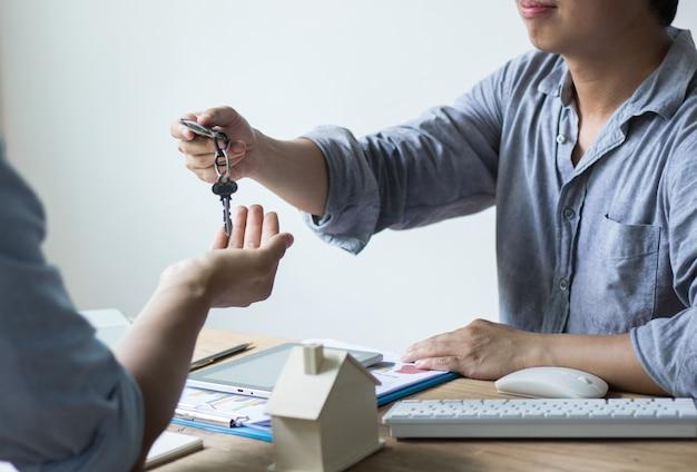 Clé de la maison donnée par le vendeur, concept de la protection des mains de l'agent de courtage d'assurance