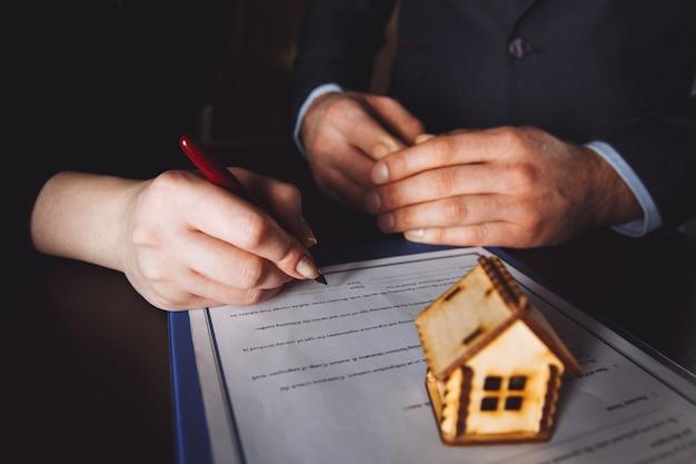 Clé de la maison en main de l'employeur de la banque pour vendre la maison après l'approbation du prêt et la signature de l'acheteur dans le papier du contrat au bureau.