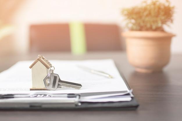Clé de la maison sur papier contract prépare pour le propriétaire sur la table