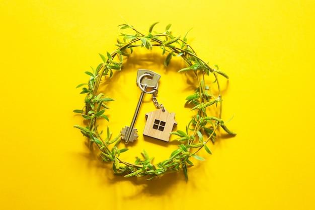 Clé de maison avec porte-clés sur fond jaune et bouquet printanier de branches avec des feuilles. ferme, hébergement touristique, réservation, emménagement dans une nouvelle maison, hypothèque, location et achat immobilier, offre d'été