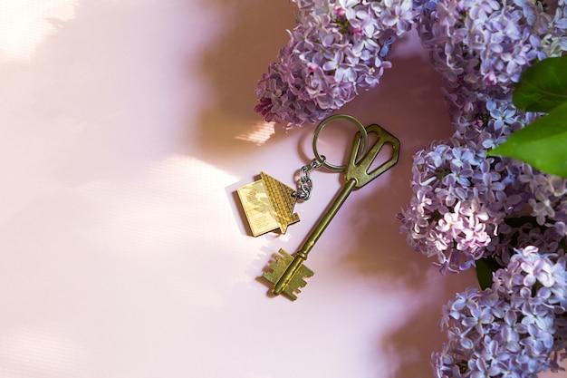 Clé de maison avec porte-clés sur fond de printemps rose et branches de lilas. maison de vacances d'été, réservation d'un chalet à la campagne, déménagement dans une nouvelle maison, hypothèque, location et achat d'un bien immobilier. espace de copie
