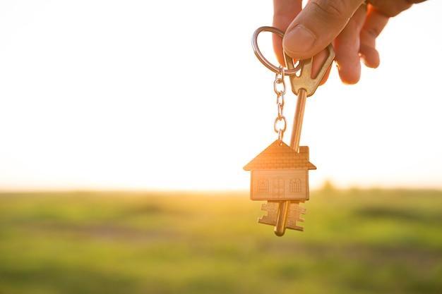 Clé de maison avec porte-clés à la main. fond de ciel, de lumière du soleil et de champ. rêve de maison, construction d'un chalet à la campagne, conception de plan et de projet, ferme, emménagement dans une nouvelle maison, logement. espace de copie