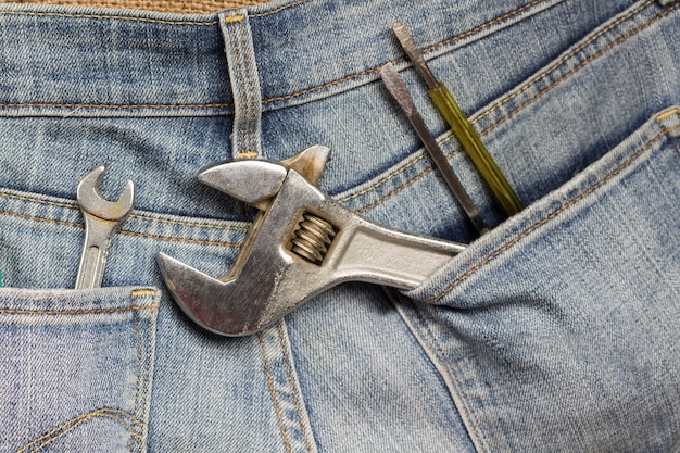 Clé à molette et autres outils de travail dans la poche de jeans. fermer