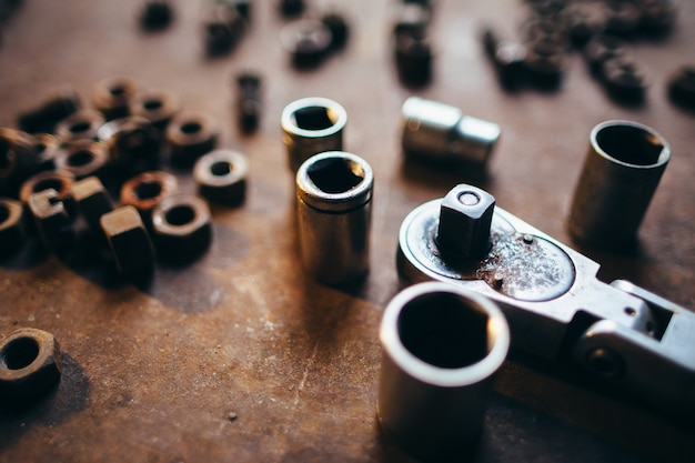 Clé à molette et écrous de vis gros plan sur une surface métallique rouillée