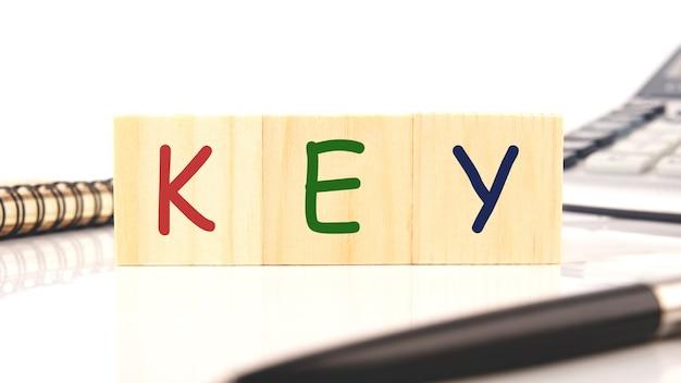 Clé de mot sur des blocs de bois à côté de stylo, calculatrice, bloc-notes sur fond blanc.