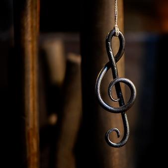 Une clé de musique en feuille métallique est suspendue à une corde dans un atelier de forgeron