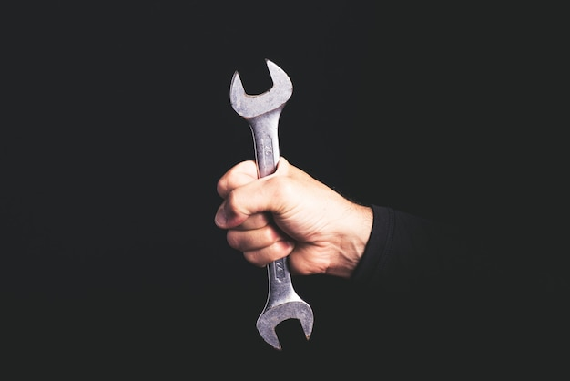Clé - outils dans une main d'homme - concept de service de maintenance