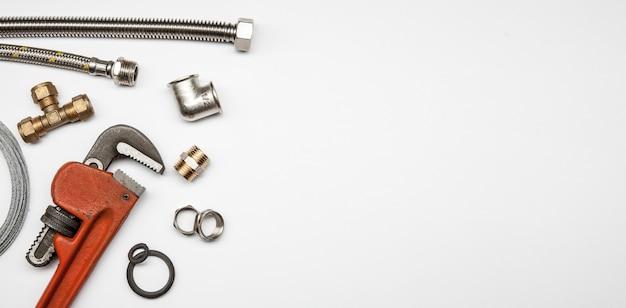 Clé, outils de plomberie, raccords et équipements sur fond blanc isolé avec copie espace