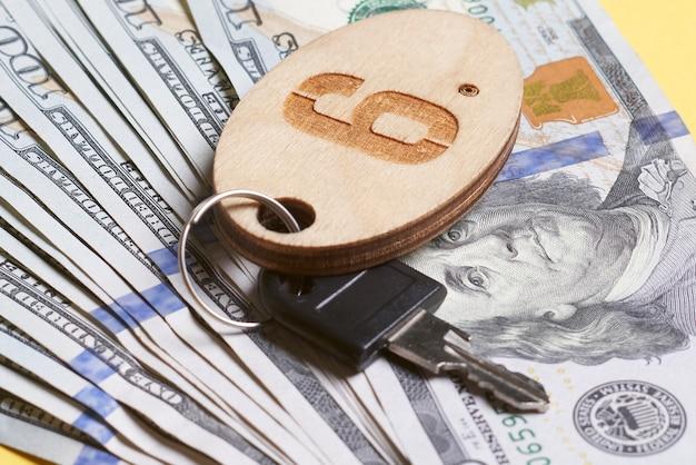 Clé sur un porte-clés avec un numéro posé sur des billets d'un dollar