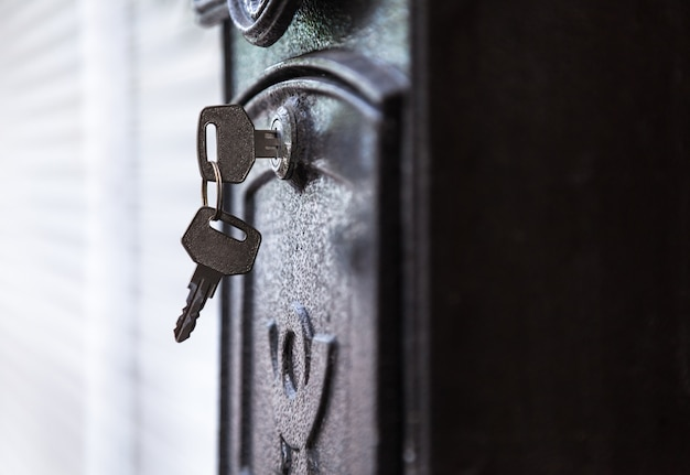 Clé de porte insérée dans le trou de serrure prêt à ouvrir la boîte aux lettres métallique noire