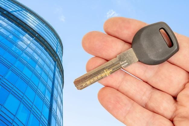 Clé de porte en métal dans la main d'un homme. vente et location de biens immobiliers.