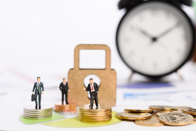 Clé pour réussir une grande part de marché, les gens d'affaires miniatures se tiennent sur des pièces d'or avec réveil