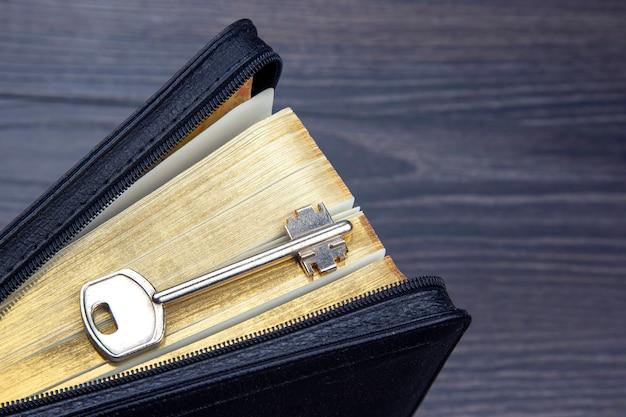 La clé se trouve sur le livre de la bible. métaphore pour découvrir la sagesse à travers l'étude de la littérature religieuse