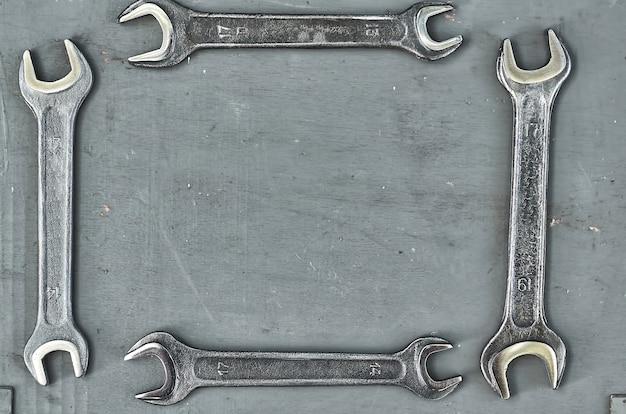 Clé sur une surface en bois peinte en gris. outils métalliques pour travaux manuels