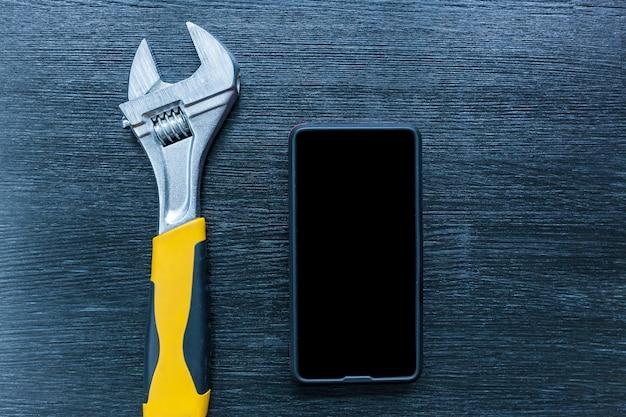 La clé avec le téléphone repose sur une table en bois noir. clé avec un téléphone sur la table..