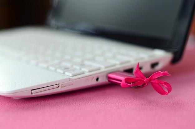 Une clé usb rose brillante avec un noeud rose est connectée à un ordinateur portable blanc, qui repose sur une couverture de tissu molletonné rose pâle et moelleux.