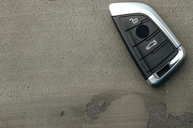 Clé de voiture automobile moderne sur béton noir close up