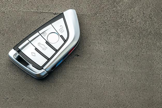 Clé de voiture automobile moderne sur fond de béton noir close up