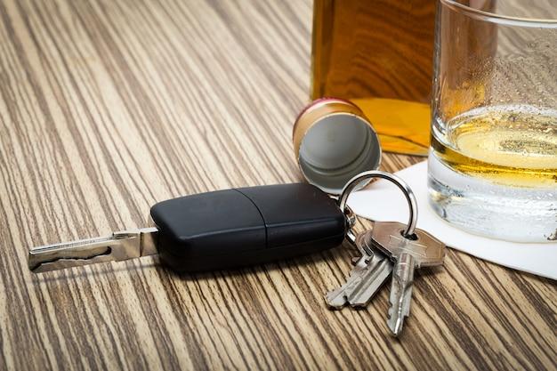 Clé de voiture sur le bar avec de l'alcool renversé