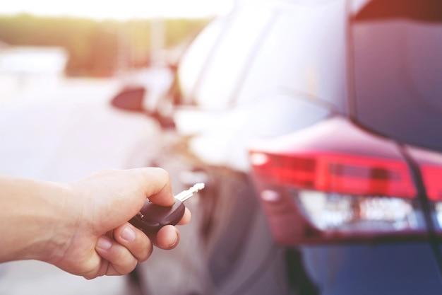 Clé de voiture dans la main de l'homme d'affaires. appuie à la main sur les systèmes d'alarme de voiture télécommandés