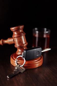 Clé de voiture juge en bois marteau et bouteille d'alcool avec verre