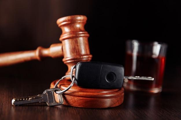 Clé de voiture juge marteau et bouteille d'alcool avec verre gros plan