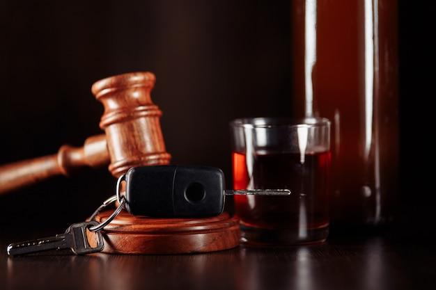 Clé de voiture juge marteau et bouteille d'alcool avec verre