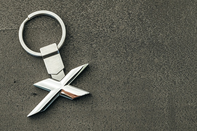 Clé de voiture lettre x métal sur fond de béton foncé close up