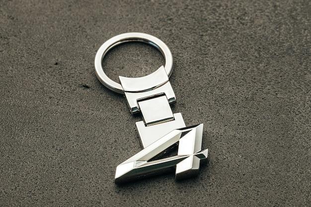 Clé de voiture numéro quatre en métal sur fond de béton foncé close up