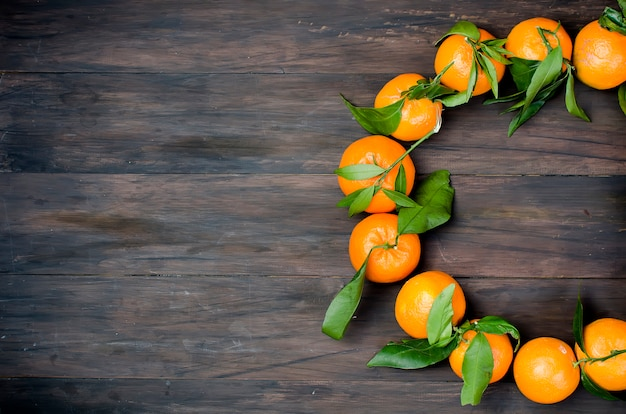 Clémentine de mandarines avec des feuilles sur une table en bois.