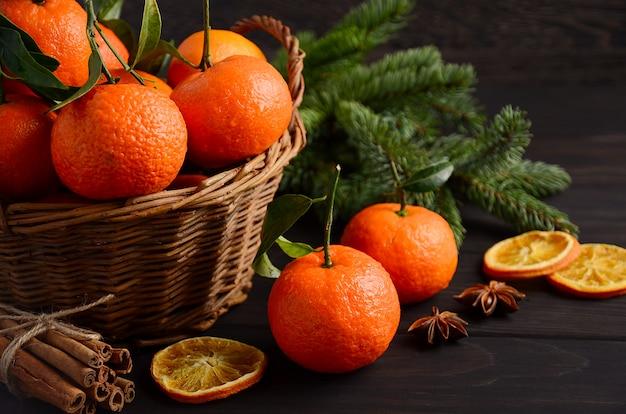 Clémentines de mandarine fraîche aux épices sur un fond en bois foncé