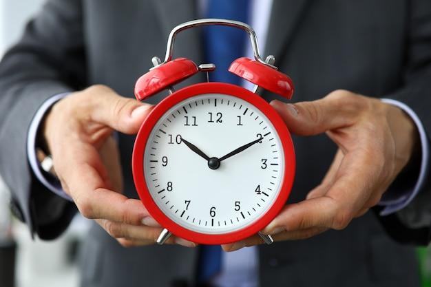 Clerk en costume et cravate tenir une horloge vintage rouge