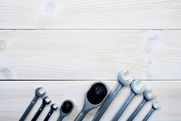 Clés de différentes tailles sur un fond en bois blanc texturé.