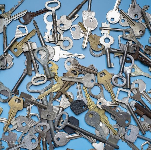Clés sur fond bleu. clés de verrouillage de porte et coffres-forts pour la sécurité des biens et la protection de la maison.