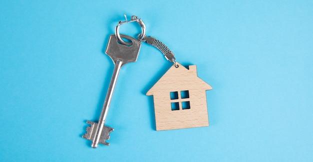 Clés de la maison avec porte-clés sur surface bleue