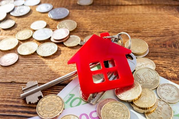 Clés de maison rouge sur le fond des billets et des pièces. concept immobilier.