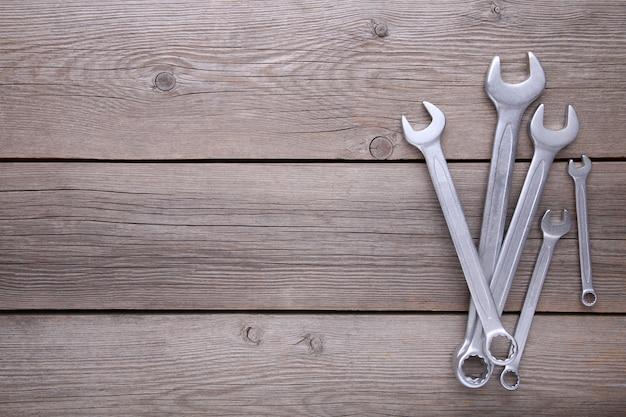 Clés mixtes à réparer sur fond gris en bois
