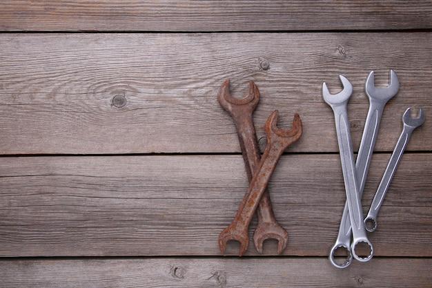 Clés neuves et anciennes à réparer sur fond gris