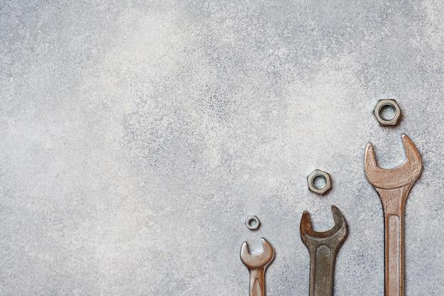 Clés, outils boulons et écrous sur fond de béton gris avec espace de copie.
