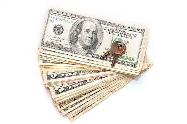 Clés et pile de dollars isolés sur fond blanc. vente et achat de biens immobiliers.