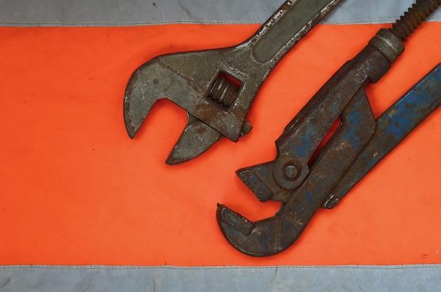 Clés à pipe et réglables sur le fond d'une chemise orange de signaleur