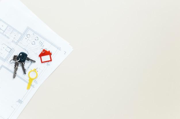 Clés et porte-clés forme maison sur blueprint sur fond blanc