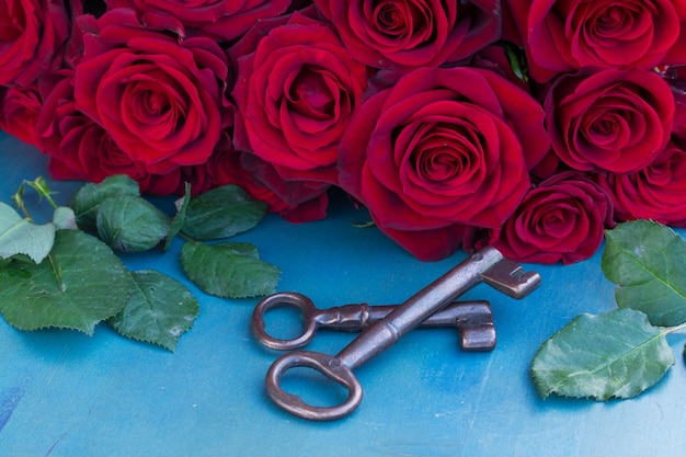 Clés avec roses cramoisies sur table bleue