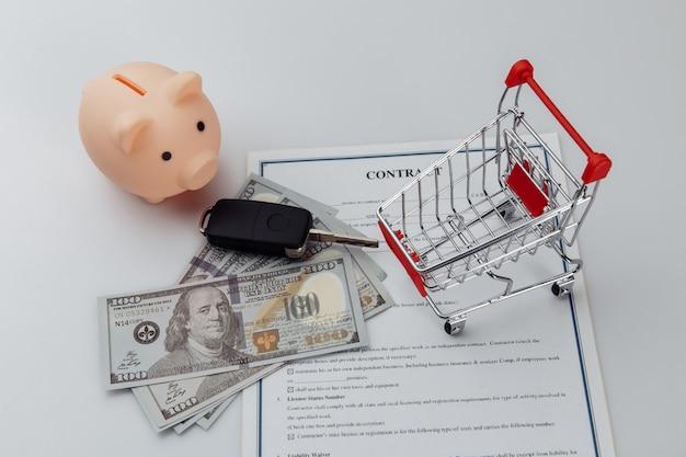 Clés de voiture, billets en dollars et tirelire sur contrat de crédit.