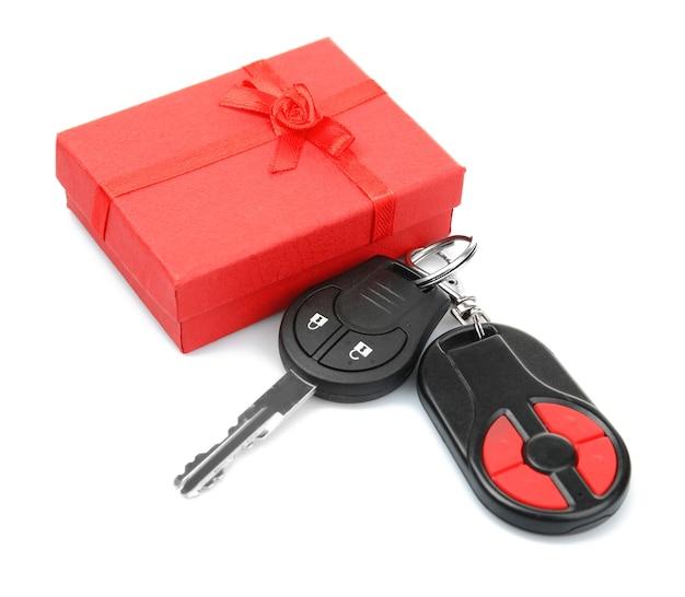 Clés de voiture et coffret cadeau sur fond blanc