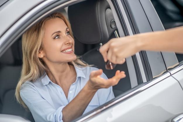 Clés de voiture. femme blonde souriante prenant les clés de la voiture et à la satisfaction