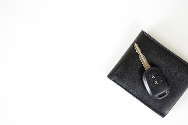 Clés de voiture sur le portefeuille isolé sur blanc avec un espace sur la gauche.