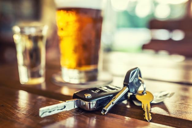 Clés de voiture et verre de bière ou d'alcool distillé sur table dans un pub ou un restaurant.